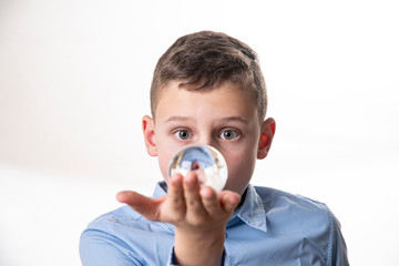 Boy sees his mirror image in a glass ball directly in front of his face against a white background