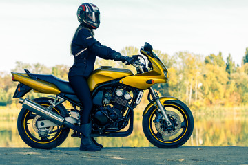 The girl in full equipment sits on a yellow motorcycle.