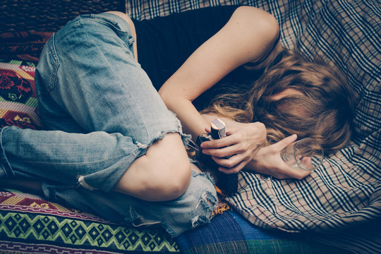 Young drunk woman on the sofa. Drug addicted, alcoholism, depression.
