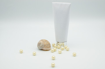 White cosmetics or medicine tube with a shell and sea pearls isolated on a white background