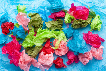 Crumpled colorful tissue paper on a blue tissue paper background