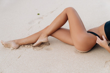 Close-up tanned parts of female body on the beach with white sand. Sexy model in a black bikini. Woman in a swimsuit on summer vacation.