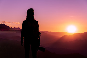 Back view of young hipster photographer holding the camera with sunset on mountain natural background.