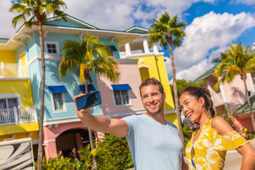 Aufkleber - Selfie photo couple tourists taking picture with smart phone in Fort Myers, Florida at colorful wood beach cottages. USA summer travel lifestyle. Asian woman and Caucasian man smiling at mobile phone.