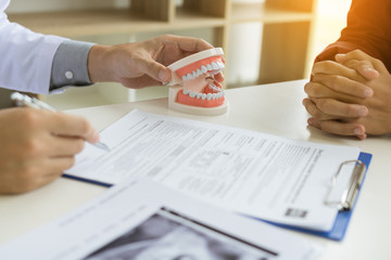 Confident dentist man holding a dentures with talking senior patient at office room.