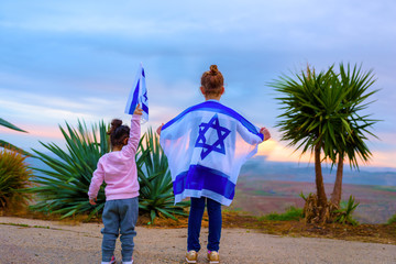 Happy girl sister friends with the flag of Israel at sunset outdoors.