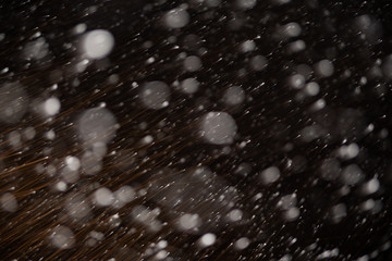 Background of falling snowflakes in the light of a lantern.