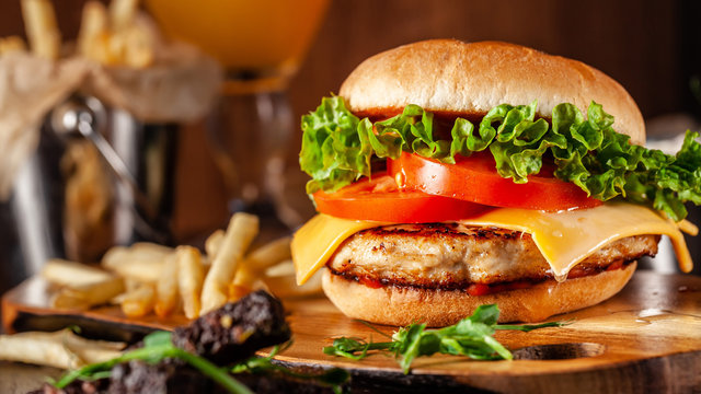 American cuisine concept. Juicy burger with meat patty, tomatoes, cheddar cheese, lettuce and homemade bun. In the background are french fries and a glass of beer. Close up