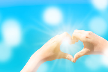 Woman hand do heart shape on blue sky  and bokeh background.