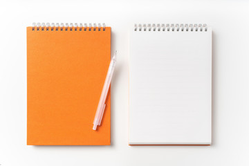 Top view of orange spiral notebook, page, pencil