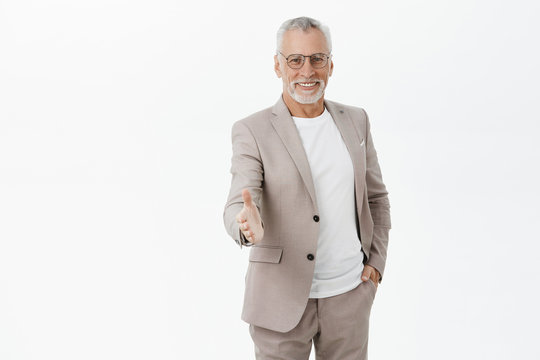 Nice to meet you. Portrait of friendly-looking optimistic and handsome senior man with grey beard and hair holding hand in pocket of suit smiling at camera pulling hand to handshake greeting student
