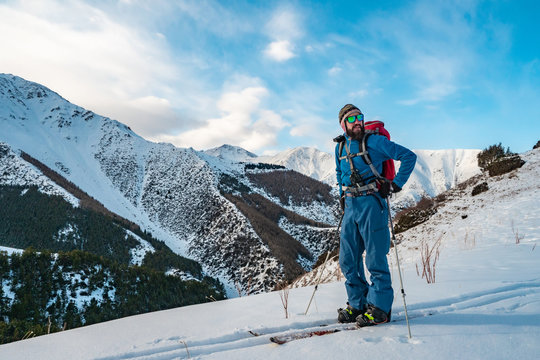 A man is engaged in ski touring on splitboarding. Sunrise in the mountains