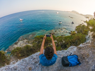 Young woman with backpack sitting on a cliff in front of the ocean using smartphone. Ponza Island coast, Italy.