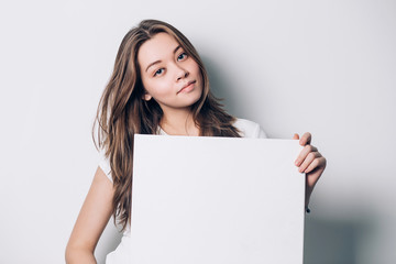 young smiling woman holding a blank sheet of paper for advertising, close-up