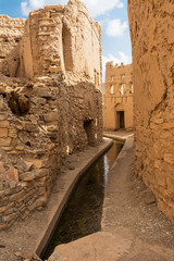 Water channeling (Aflaj) in the alleys between the semi-abandoned mud houses of Birkat Al Mouz