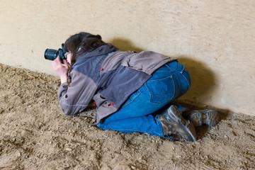 Fotograf kniet im Sand um eine interessante Perspektive zu erhalten