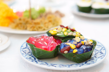 Thai pudding with coconut topping or thai sweet dessert with corn and red bean and millet in banana leaf cup and white dish on table for food