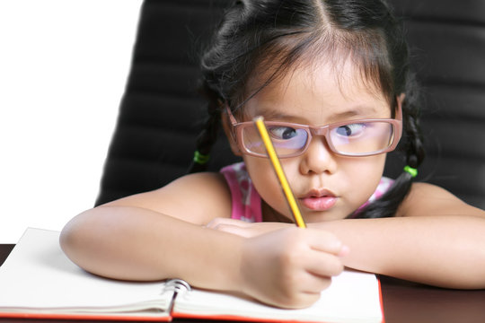 asian child or kid girl strabismus or squint-eyed make lasik with enjoy doing homework or learn write on white paper book and wear eyeglasses for short sighted on desk or table, clipping path on white