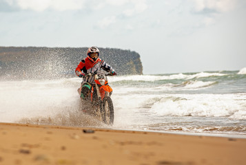 Motorcyclist in a protective suit rides a motorcycle on the sea, splashes fly from under the wheels.