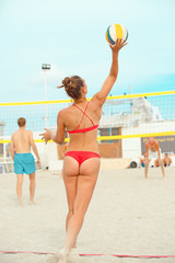 Volleyball beach player is a female athlete volleyball player getting ready to serve the ball on the beach.