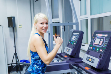 A young girl with a smile running on the treadmill in the gym.