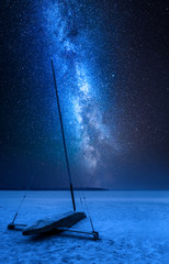 Milky way over ice boat on frozen lake at night