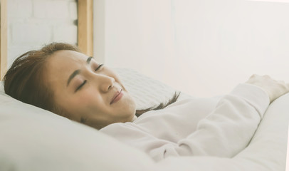 Asian woman sleep on  white pillow on bed in bedroom in holiday.happy relax time.color tone