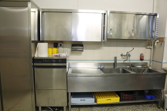 wide  kitchen with large steel sink and industrial dishwasher
