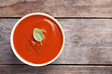 Bowl with fresh homemade tomato soup and space for text on wooden background, top view