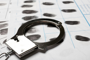 Police handcuff and criminal fingerprints card, closeup