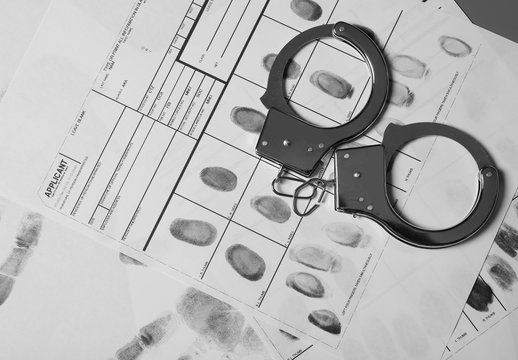 Police handcuffs and criminal fingerprints card, top view