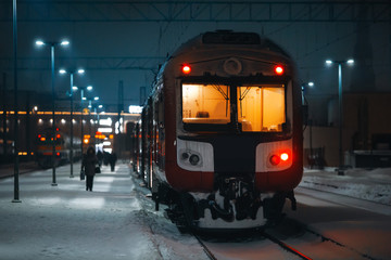 Boarding to train on railroad station during snowing at night