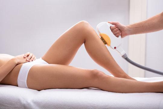 Beautician Using Laser Machine On Customer's Leg