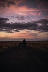 Chico caminando en la carretera hacia el infinito