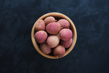 Ripe lychees on a black table. Top view.