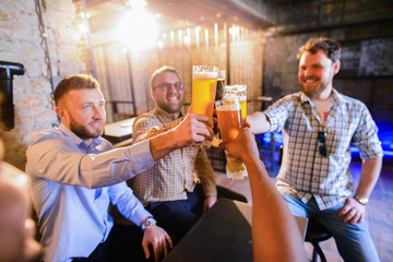 Group of young happy man sitting in a pub and clinking with glasses full of bear. Man night out. Wall mural