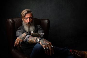 Porträt eines nachdenklichen Geschäftsmannes, der in einem Sessel sitzt und relaxt
