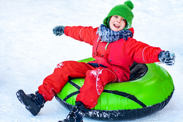 Happy child riding a tubing. Winter outdoor activities. Snowy Christmas Holidays