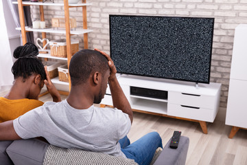 Couple Sitting Near Television With No Signal