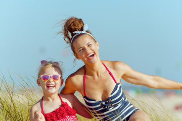 smiling modern mother and child on beach having fun time