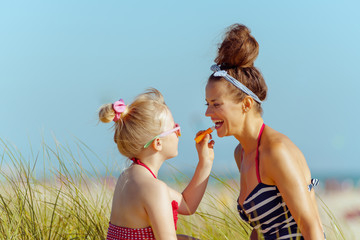 happy mother and child applying lipstick with spf on seacoast