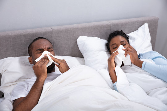 Sick Couple Lying On Bed Blowing Their Nose