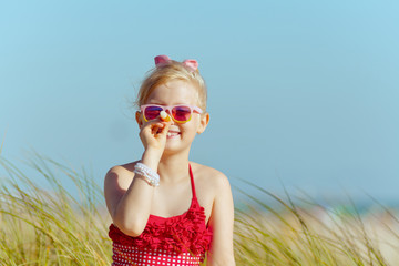 happy child makes nose from lipstick with spf on ocean shore