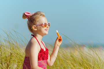 child looking into distance while holding lipstick with spf
