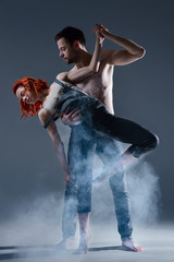 Couple in love dancers making dance element in smoke fume on isolated grey background scene. Redhead woman female dancer athlete gymnast in overalls with muscle male man in jeans and bare naked torso