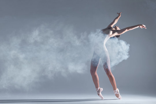 Elegant woman female girl ballerina dancer in beige body pointe shoes dancing, making performance and dance element in fog dust smoke fume on isolated grey background scene. Dancing in cloud concept