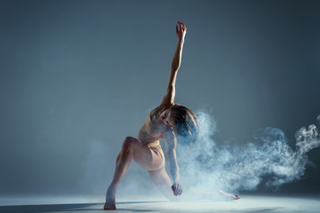 Dancing in cloud concept. Muscle brunette beauty female girl adult woman dancer athlete gymnast in smoke / fog wearing dance bodysuit making dance element performance on isolated grey black background Fototapete