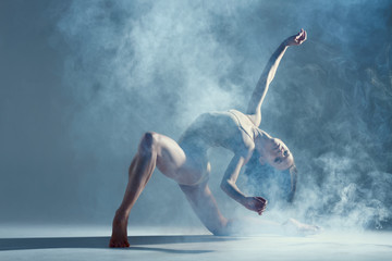 Dancing in cloud concept. Muscle brunette beauty female girl adult woman dancer athlete in fog smoke fume wearing dance bodysuit making emotional dance element performance on isolated grey background