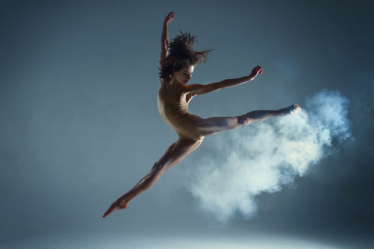 Dancing in cloud concept. Muscle brunette beauty female girl adult woman dancer athlete gymnast in smoke fog wearing dance bodysuit jumping in mid air, performance on isolated grey / black background