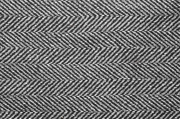 Herringbone fabric, texture background. Black and white tweed pattern, weaving, textile material.